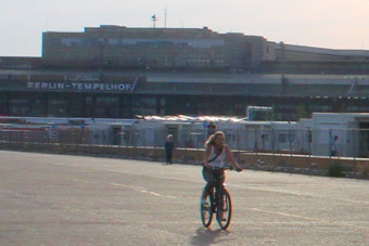In the background: the buildings of Berlin-Tempelhof airport, in front of it the refugees' village, and in the forefront a woman cycling on a former landing strip
